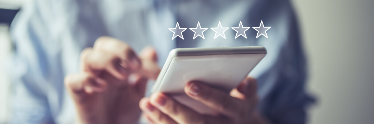 Close up of man holding a mobile phone with 5 stars above the device