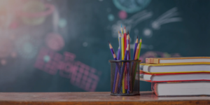 colored pencils and stack of books in front of a chalkboard