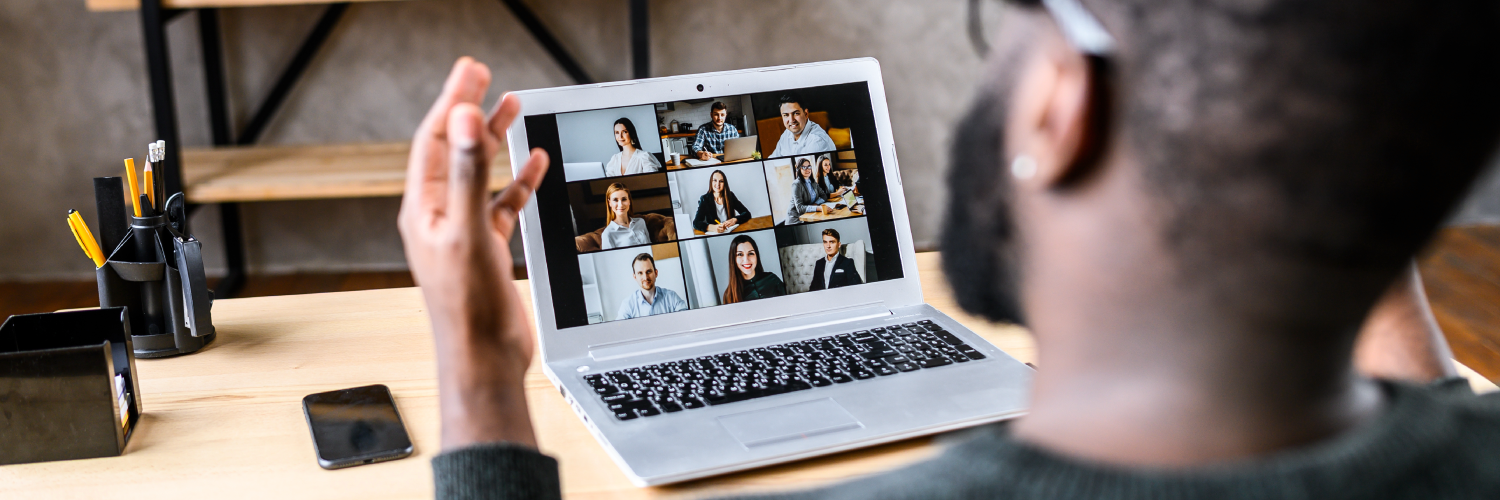 Man sitting at a desk video conferencing with nine other people on laptop