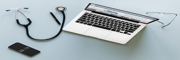 overhead view of stethoscope, laptop, cellphone, and glasses