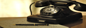black rotary phone on top of paper
